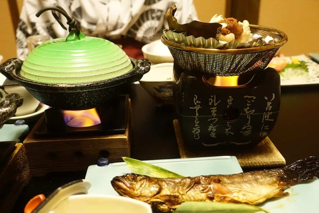 Dishes are heating on the table of the private dining room of the ryokan Yunoyado Motoyu club