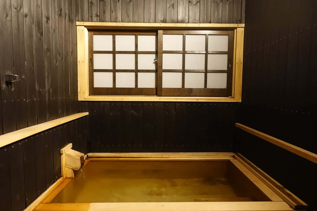 Private onsen bath seen from the front of a room of the ryokan Yunoyado Motoyu club