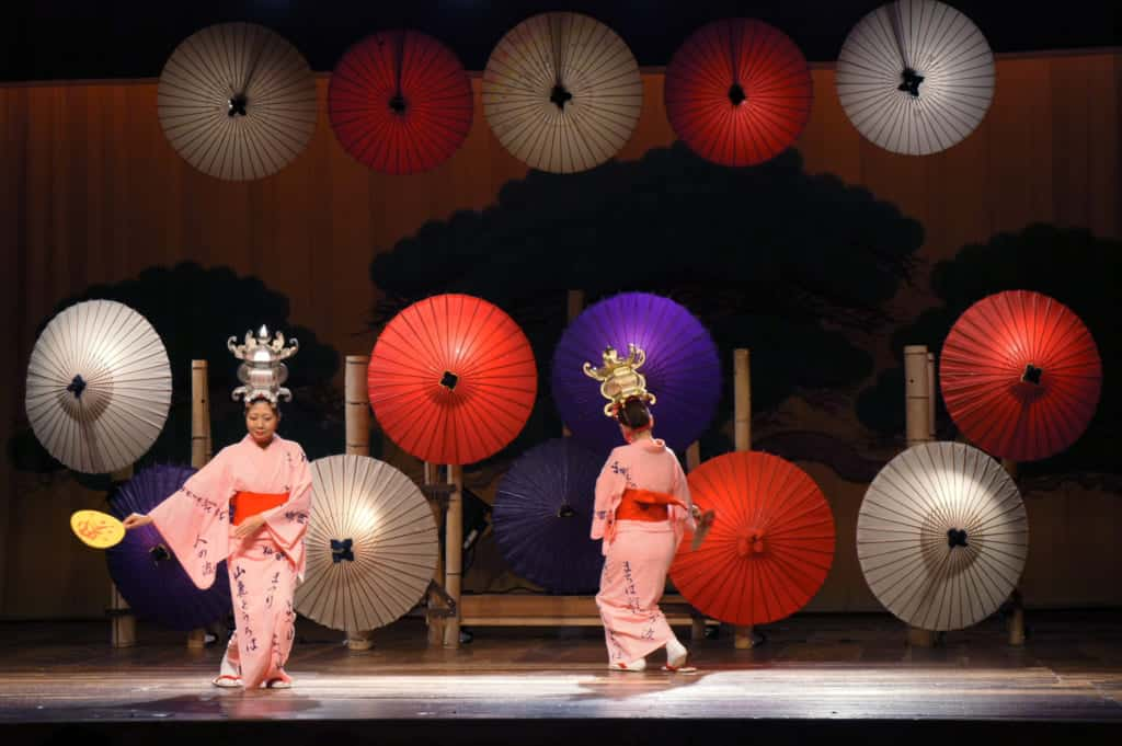 Two dancers, performing Yamaga lantern dance in front of paper umbrellas