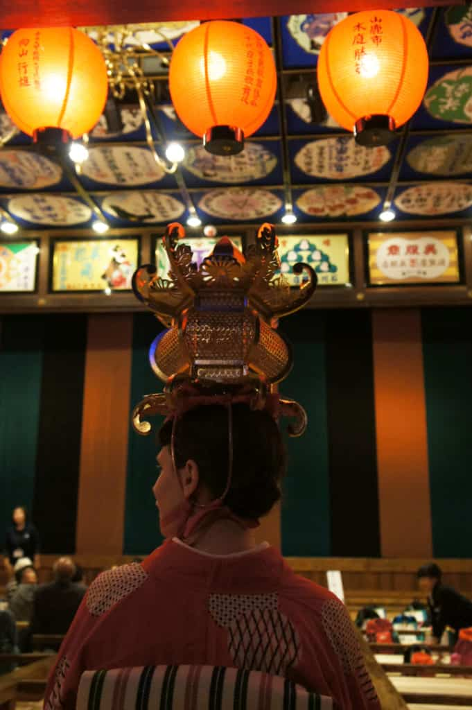 Clémentine seated in the yachiyo-za theatre, a Yamaga lantern on her head