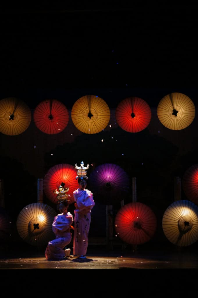 The two dancers standing in the dark, their lanterns glowing