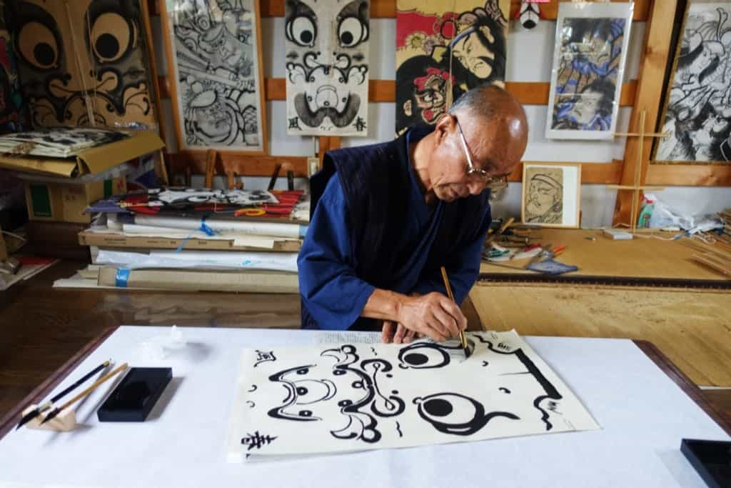 A craftsman painting the outlines of a character on a traditional kite in his workshop in Yuzawa, Akita Prefecture