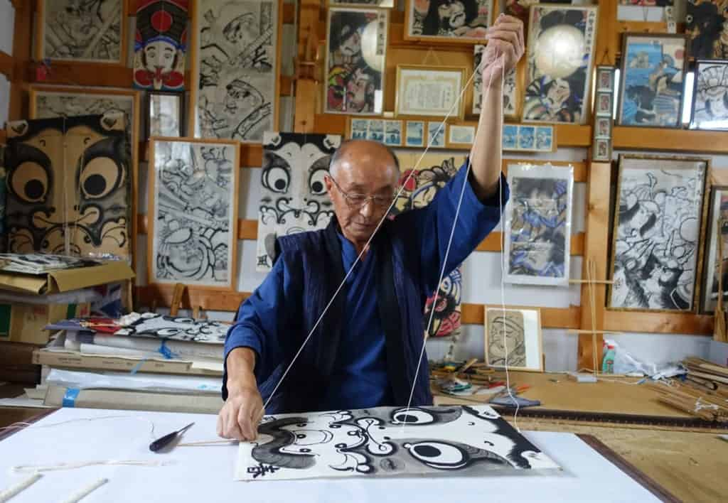 The craftsman hangs the strings that will allow the traditional kite to fly