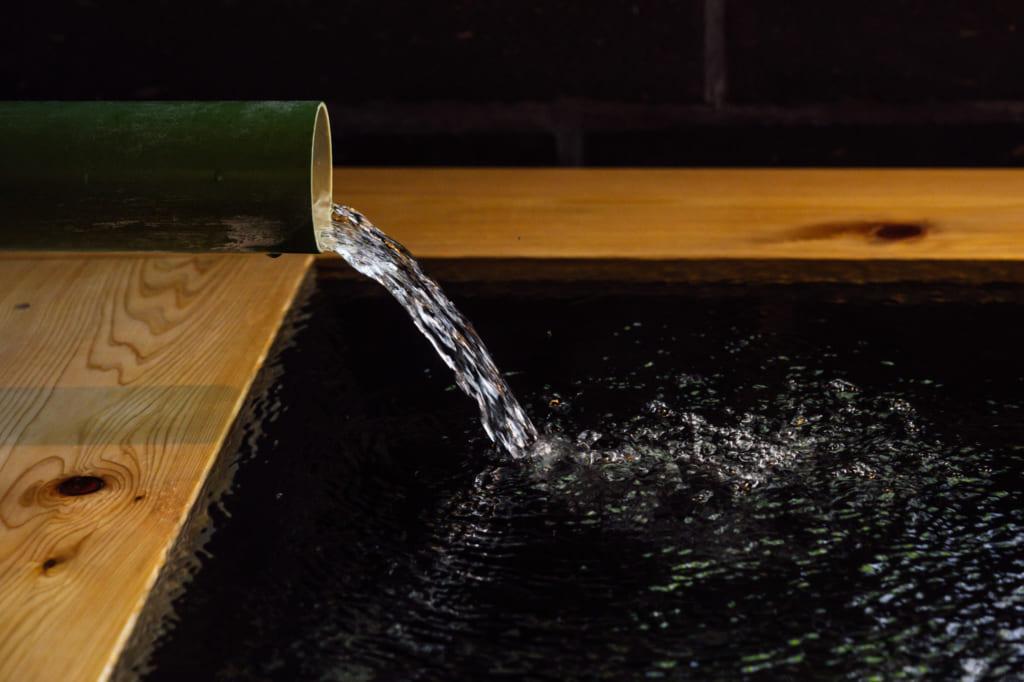 Gros plan sur l'eau qui coule dans le bassin en bois