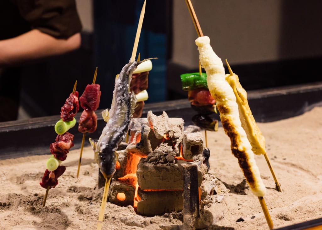 Brochettes, en train de griller autour de charbons ardents, à Kumamoto