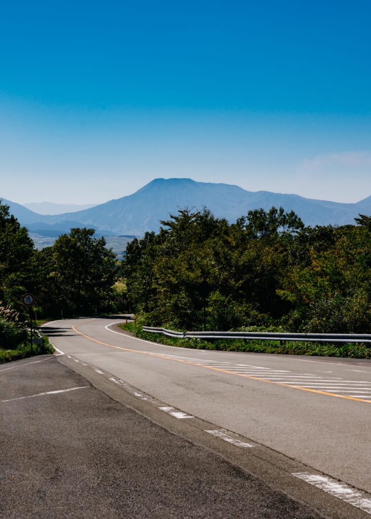 La route descend dans un paysage de montagne à Aso , Kumamoto