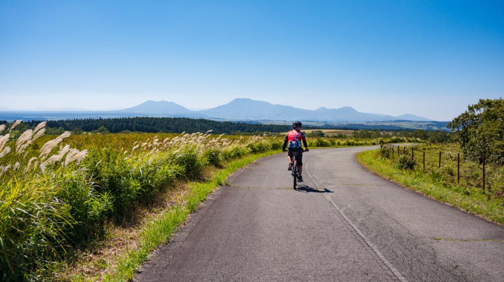 Le guide sur son vélo sur les routes de la caldeira du mont Aso