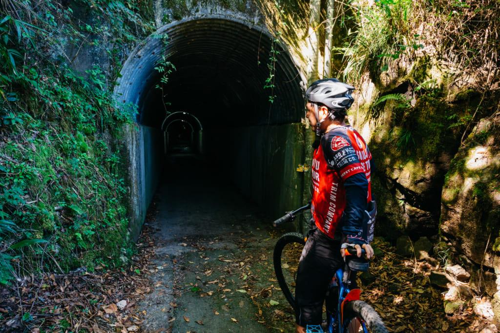 Abe san devant l'entrée d'un étroit tunnel, traversé lors des promendes à vélo à Aso