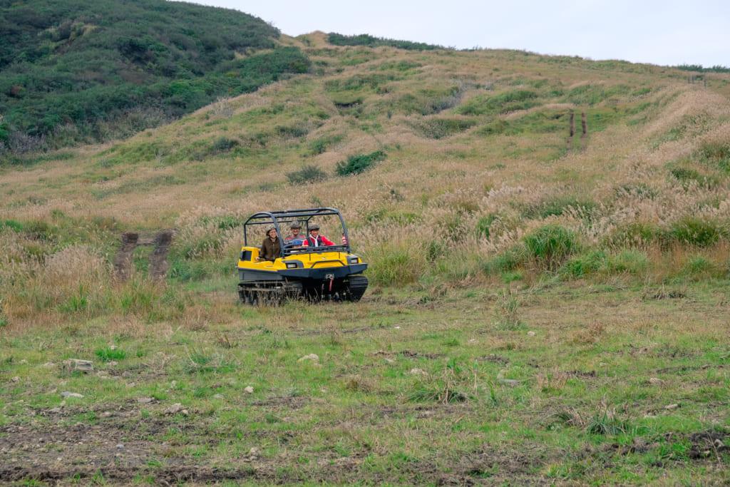 Véhicule tout terrain jaune, dans le paysage du mont Aso