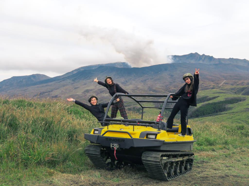 Mika accompagnée de deux autres personnes posent sur le camion tout terrain devant une éruption du mont Aso : une des activités de plein air à pratiquer à Kumamoto