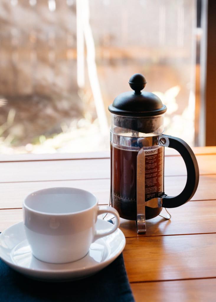 Cafetière à piston et tasse sur la table baignée de soleil