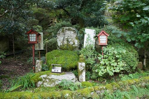 Statue de pierre entourée de deux lanternes vermillon, dans la région Rokugo Manzan située dans la péninsule de Kunisaki, Oita, Kyushu