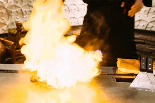 Chef d'un restaurant de style Teppanyaki enflammant la pièce de boeuf Kobe