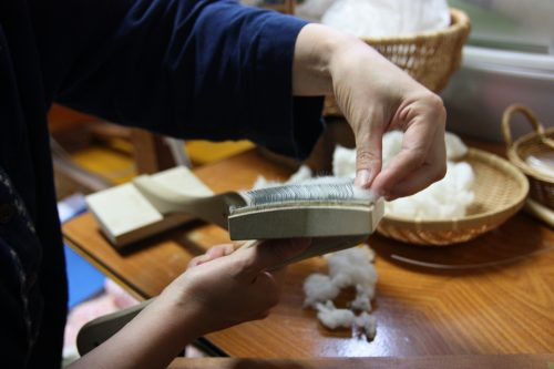 Lisser les fibres de coton avant de fabriquer le Yumihama-gasuri, à Yonago, préfecture de Tottori, Japon