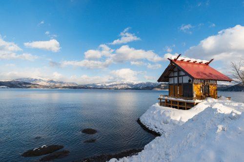 Petit sanctuaire de Kansagu dans la neige au bord du lac Tazawako, Akita, Japon