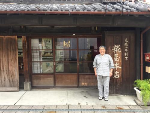 Mme Asari devant la façade traditionnelle de sa fabrique de koji à Saiki, Oita