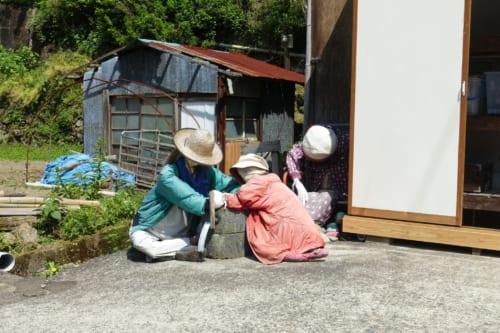 Épouvantails de tissus devant des bâtiments sur le chemin du sanctuaire d'Akimoto