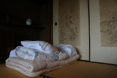 Futon plié, posé sur les tatamis devant des parois peintes à l'encre