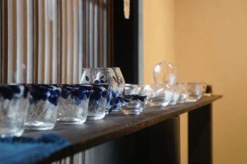 Verres et autres pièces en verre soufflé réalisées à Asuka, exposées dans une maison traditionnelle.