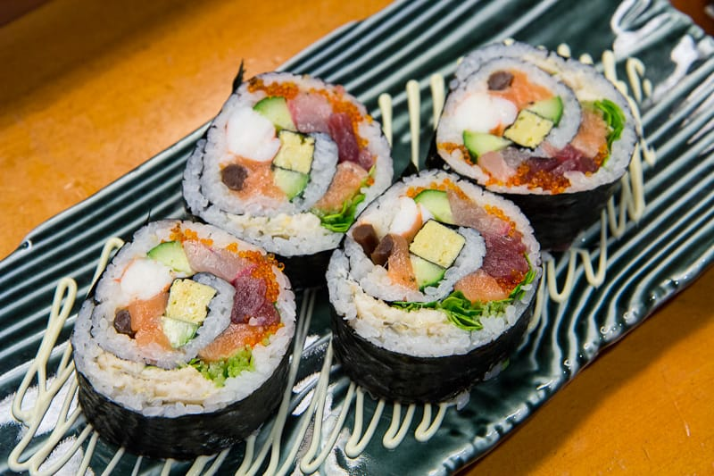 """""""Rainbow Roll"""", a very thick futo maki with no less than 15 ingredients wrapped in sushi rice and dry seaweed"""