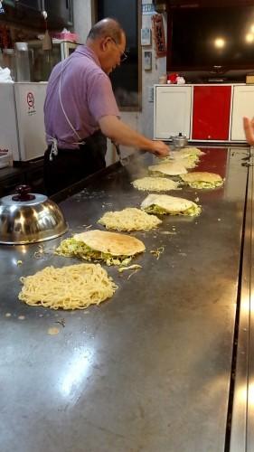 Juju Okonomiyaki restaurant where Okonomiyaki is being grilled.