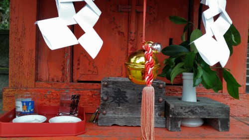Close up of a little shrine with a bell hanging down at Toyotama shrine in Kagoshima.