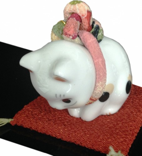 A bowing cat statue used to help explain the Japanese concept of sorry or sumimasen.