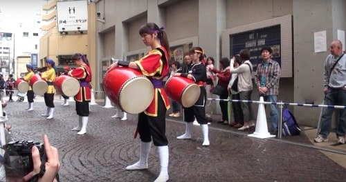 Okinawa Eisa festival: Ladies dressed in red and black playing taiko drums