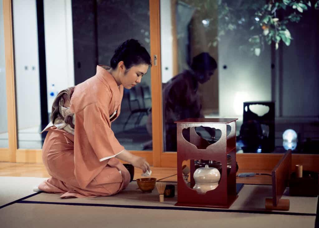woman in iromuji kimono performing tea ceremony