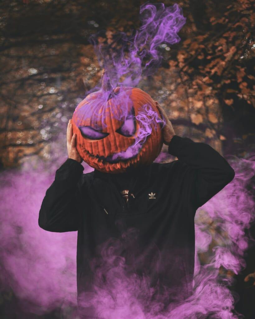A boy wearing a Halloween Pumpking mask