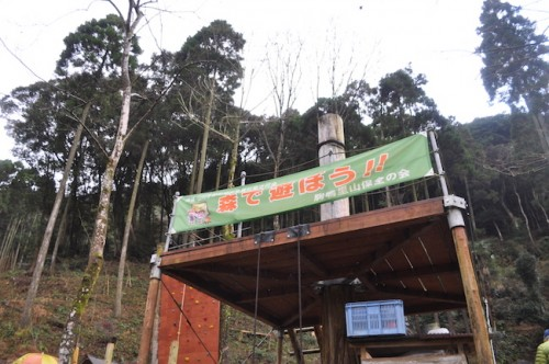 """A zipline post Nozaki-san built with a sign that reads: """"Let's play in the woods!"""""""