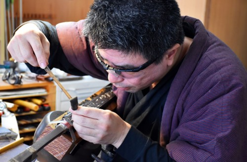 A skilled engraver at Bizen Osafune sword museum working on a blade