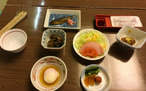 Natto, baked fish, miso soup, salad, soft-boiled egg, rice, and boiled vegetables