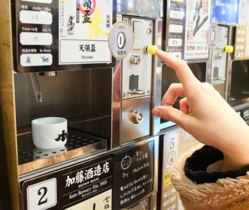 Getting sake from a vending machine at Ponshukan, Echigo-Yuzawa Station.