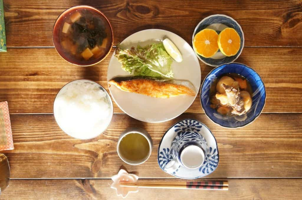 Traditional Japanese meal with rice, fish, and miso soup, served during a farmstay in Japan