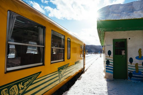 Akita Nairiku Train stops at a snowy station in Akita Prefecture.
