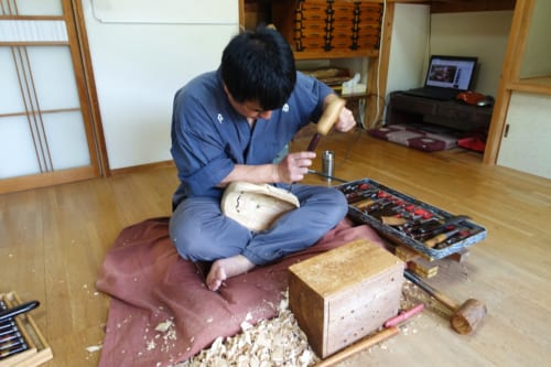 A Takachiho master craftsman works on a kagura wooden mask.