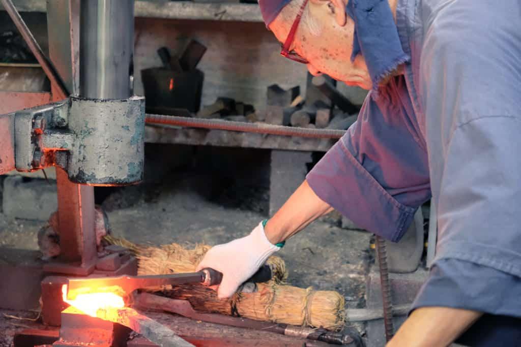Traditional Japanese sword maker in Kumamoto hammering red iron