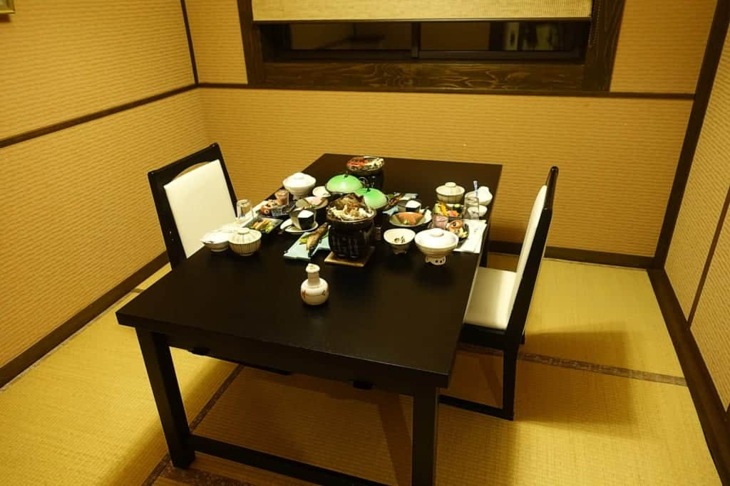 Private dining room of the ryokan where a traditional kaiseki meal is placed on the table