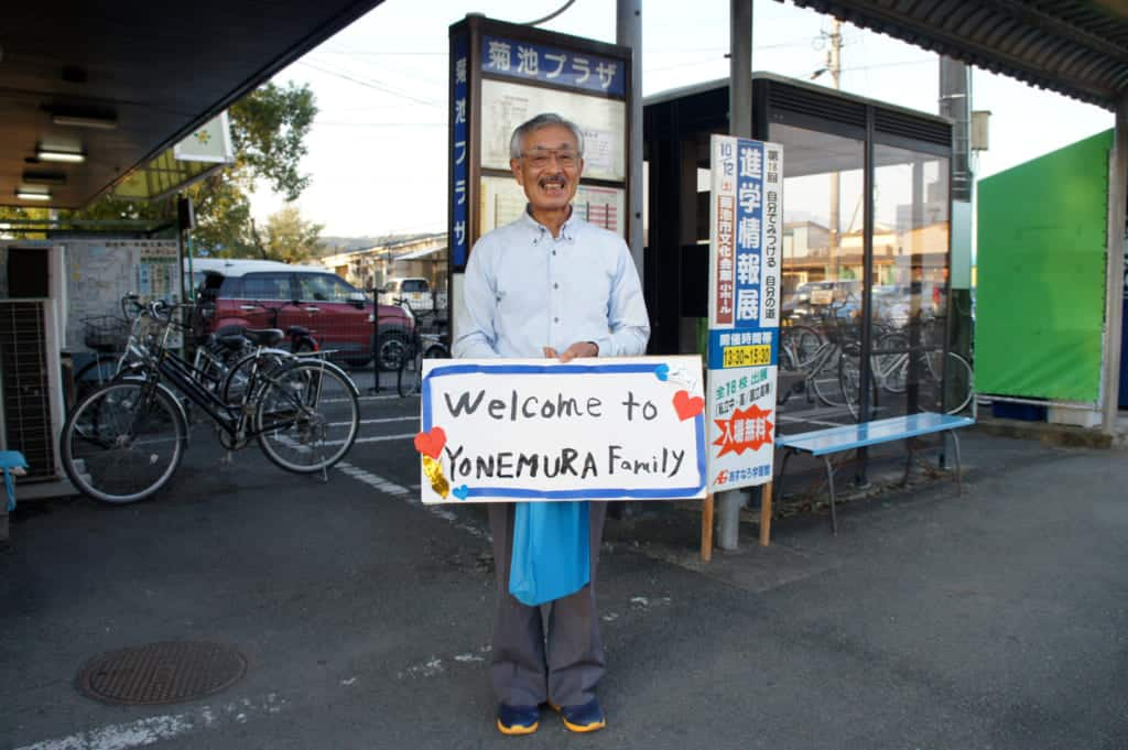 "Mr Yonemura, holding a sign written ""Welcome to Yonemura family"""