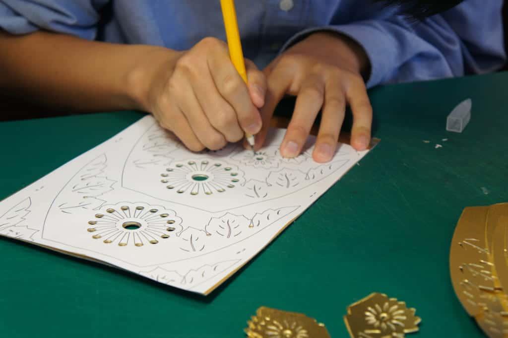 Hads of a craftman, cutting paper to make a Yamaga lantern
