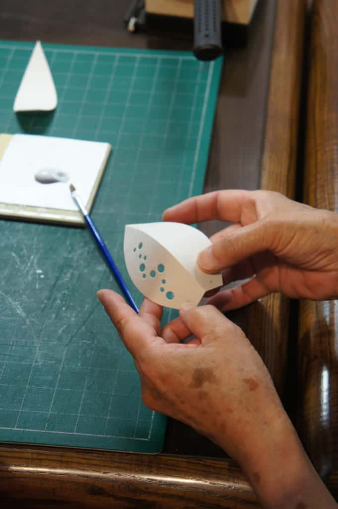 The craftswoman showing how to stick paper pieces