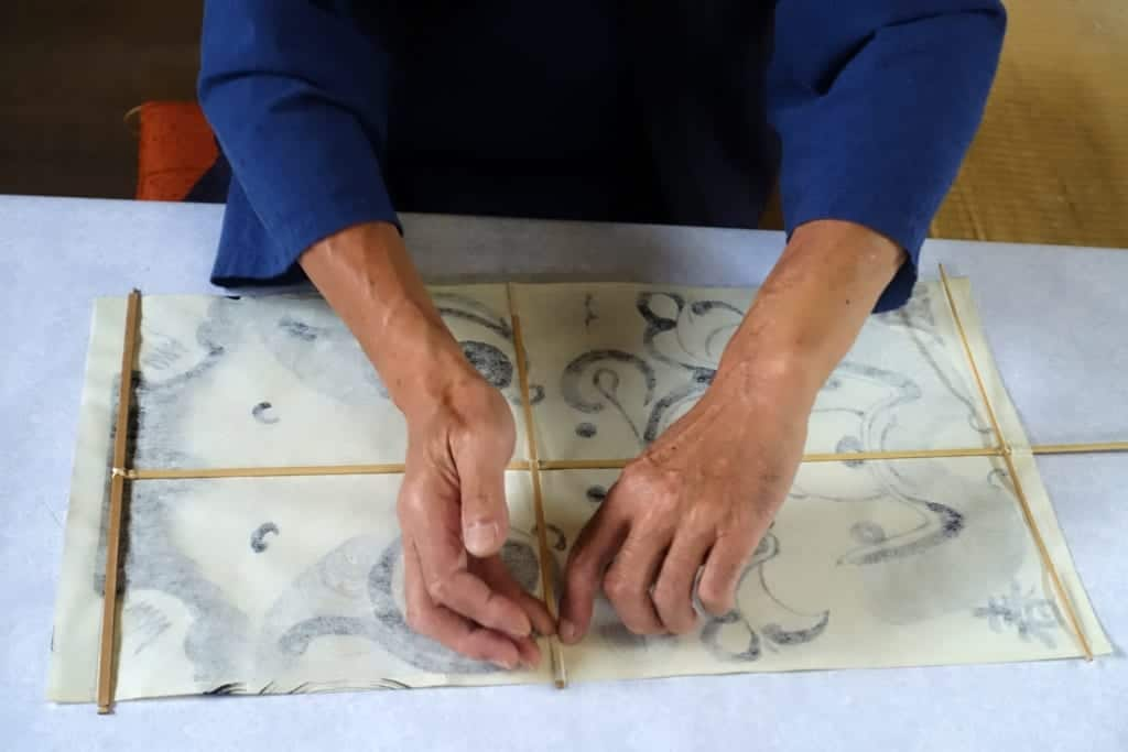The craftsman carefully places the bamboo frame of the kite on the hand-made wallpaper