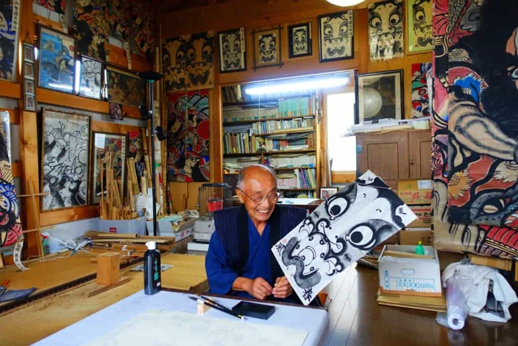 Mr. Ono smiling, posing with his finished kite in his workshop in Yuzawa, Akita Prefecture