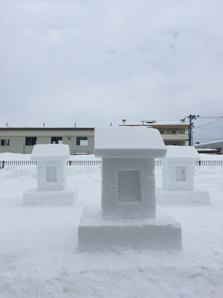 Sculptures of temples and dogs in the snow during the Inukko Matsuri festival