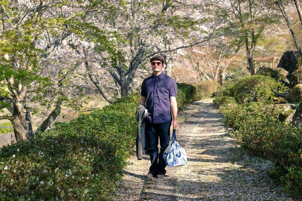 man standing in traditional japanese park during sakura cherry blossom season in japan