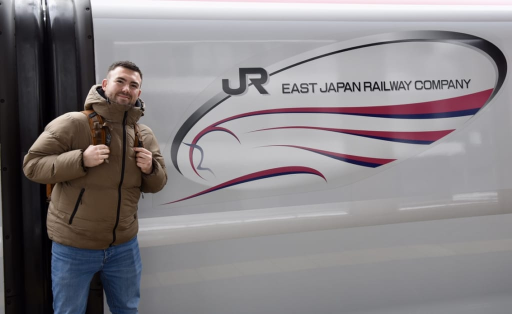 Standing in front of the Shinkansen with logo