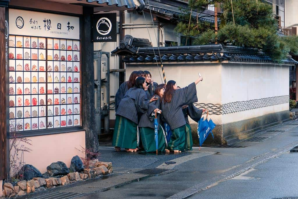 girls in yukatas pose on the street at kinosaki onsen