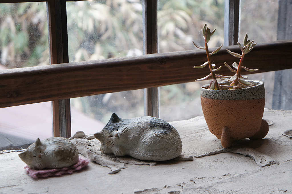 Clay figurines of two cats and a pot plant
