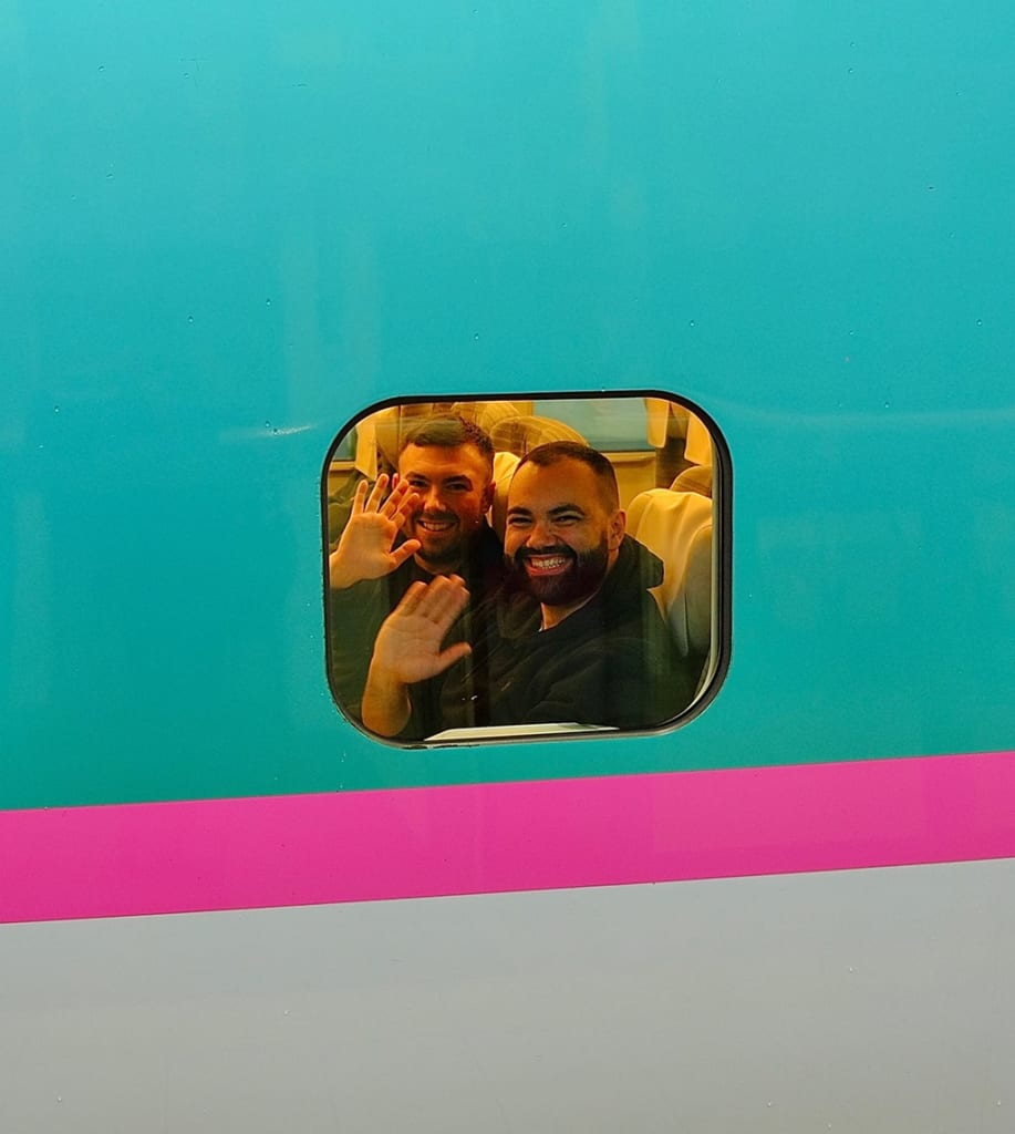 Mark and Jonathan waving from window of Shinkansen